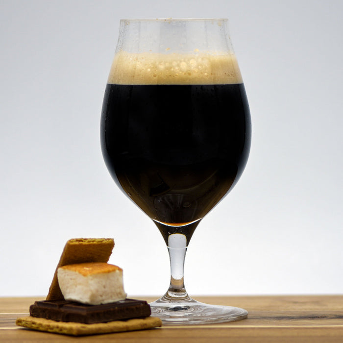 A glass of Smore's Pastry Stout with a Smores beside it