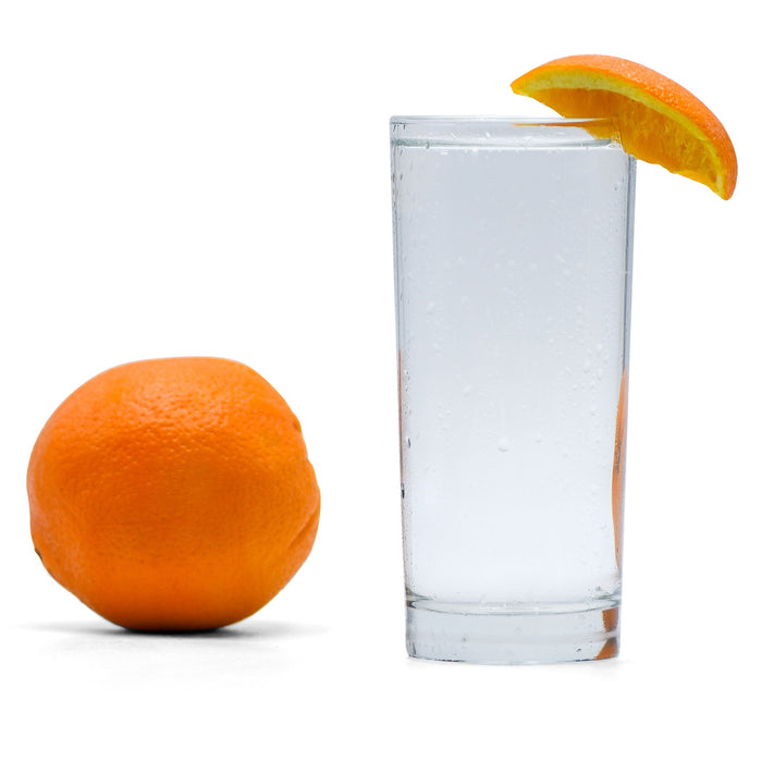 A glass of Navel Orange Hard Seltzer with an orange wedge next to a whole orange