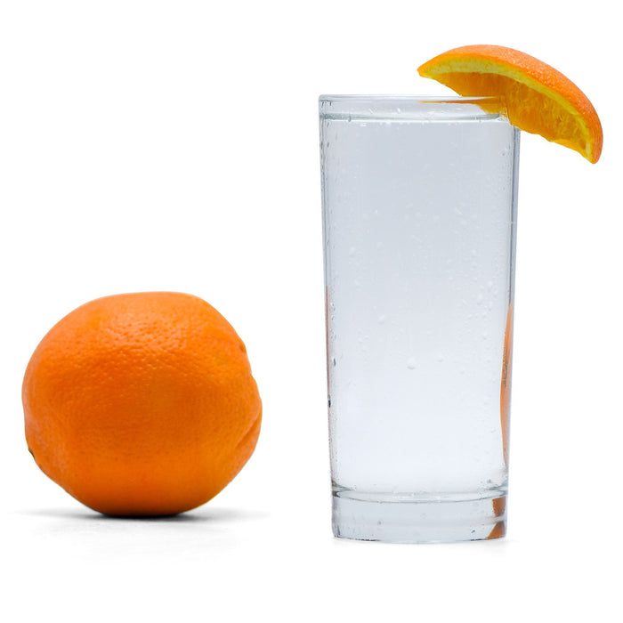 Navel Orange Hard Seltzer in a glass with an orange wedge next to a whole orange