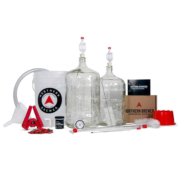 Two glass carboys with airlocks, a fermentation bucket, bottle capper with caps, racking cake, recipe kit, tubing, carboy brush, beer recipe kit, and carboy drier