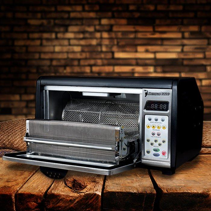 The Behmor 1600 Plus Coffee Roaster on a table in front of a brick wall with its door open