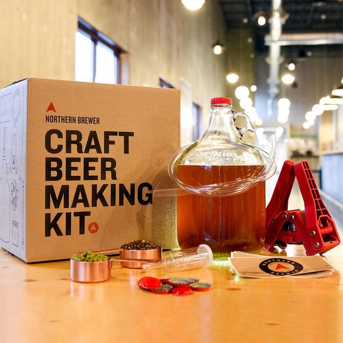 Craft beer making kit box with a fermenting carboy, bottle capper, and bottle labels on a table