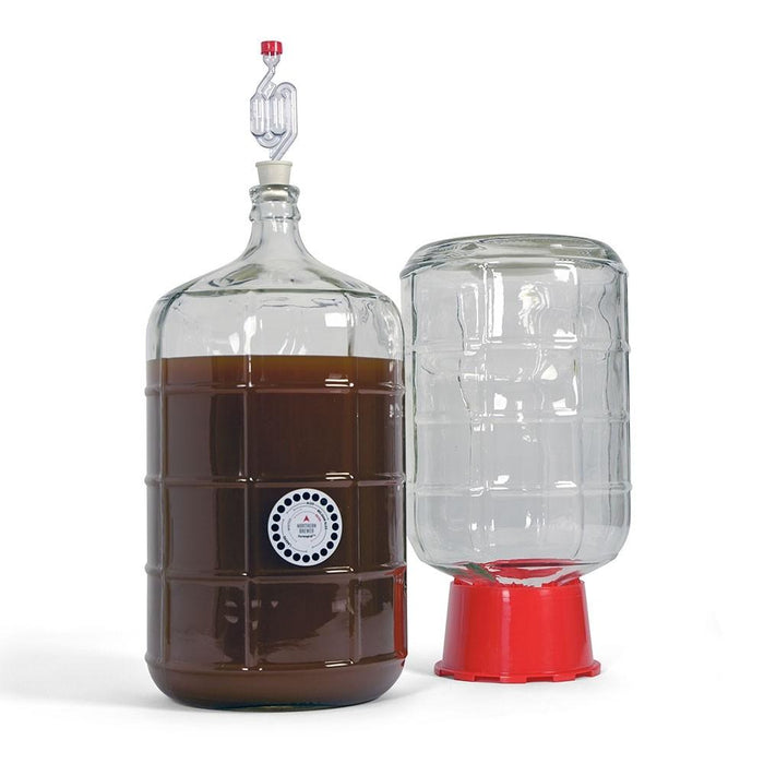 A filled carboy with adhesive thermometer and airlock, adjacent to a carboy in a carboy dryer