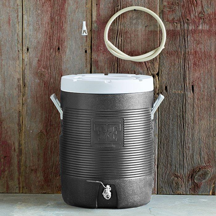 Fermenter's Favorites® Cooler Hot Liquor Tank with tubing hanging on the wooden back wall