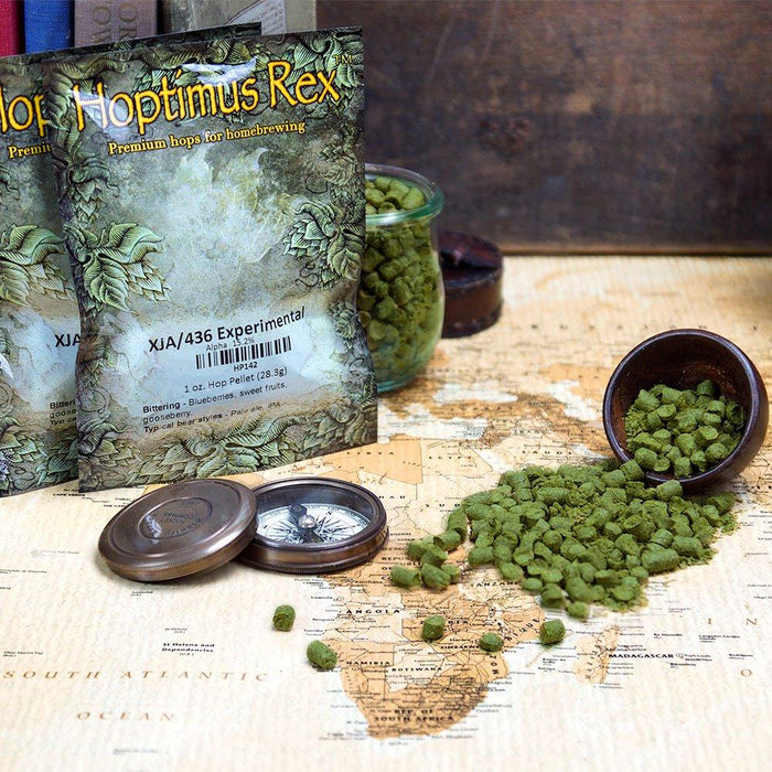 XJA/436 Experimental Hop Pellets spilling out of a display bowl onto a map of africa beside a compass and the pellet's packaging