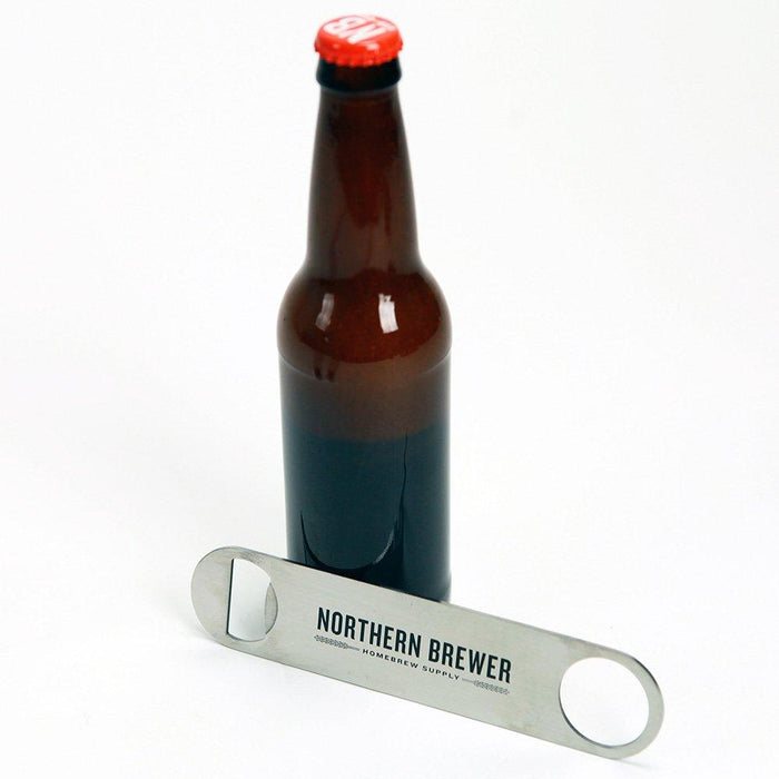 NB large paddle style bottle opener next to an amber bottle