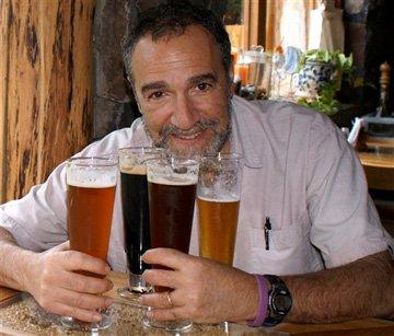 A smiling man with four beers of various styles.