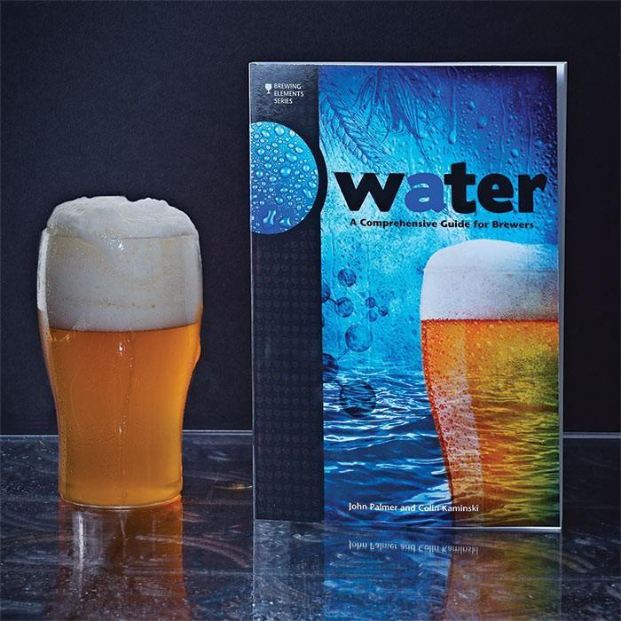 Water: A Comprehensive Guide for Brewers standing up beside a glass filled with homebrew
