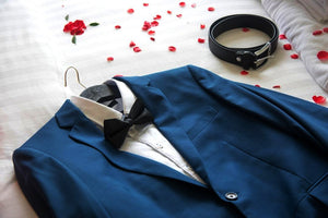 A grooms' suit laid out on a bed