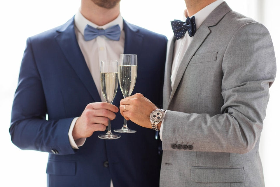 2 men in suits clinking champagne glasses