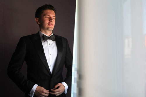 Man in tuxedo looking out window