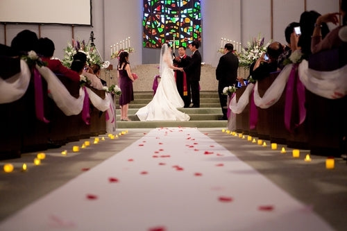 bride and groom at alter from view of aisle