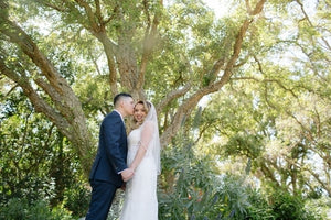 Bride and groom share kiss under tree
