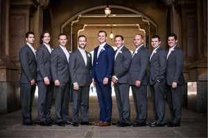 8 groomsmen and groom in archway smiling