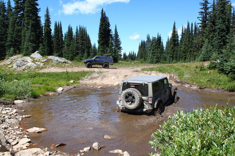 jeep in muddy trail water on sunny day