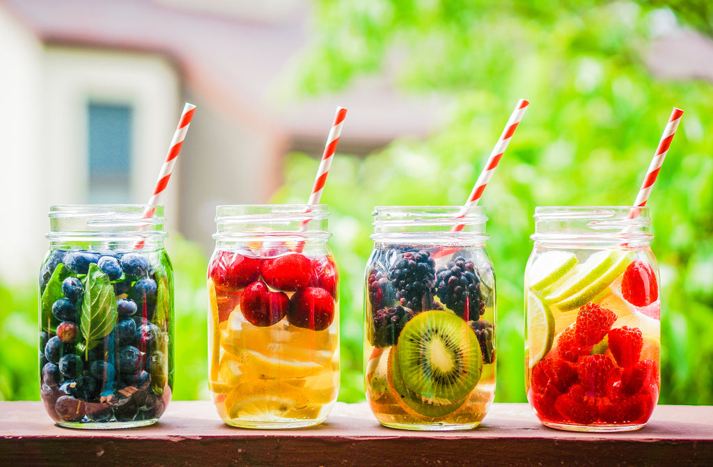 fruit infused water in mason jars with straws to stay hydrated