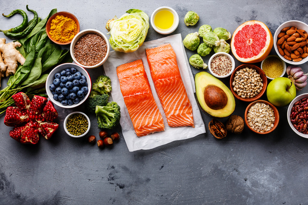 grouping of superfoods - avocados, berries, salmon, leafy greens