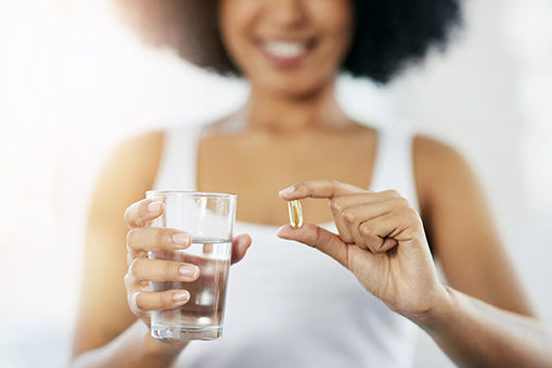 woman taking an omega 3 supplement with a glass of water - omega 3 plus and omega longevity