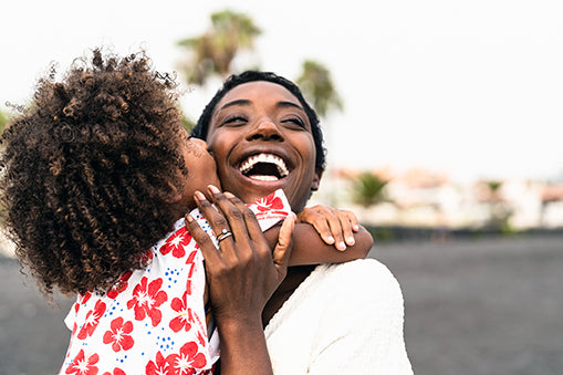 black woman hugging daughter happy