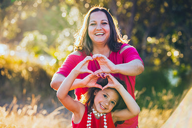 woman in field with daughter both making hearts with hands - omega 3 and heart health