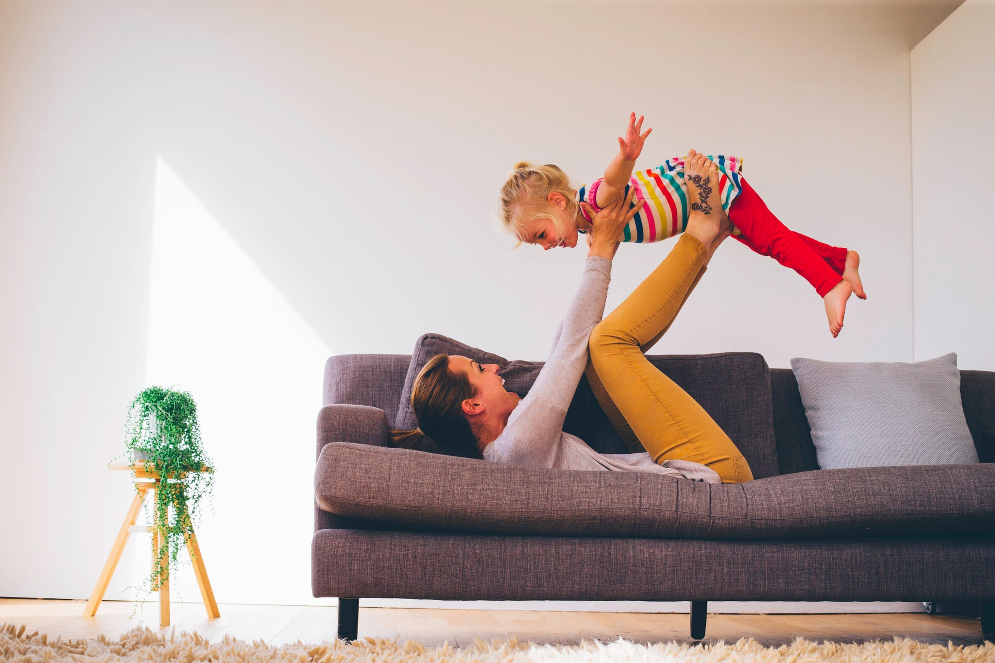 busy mom doing superman airplane flying with her daughter on the couch - aceva supplements for moms
