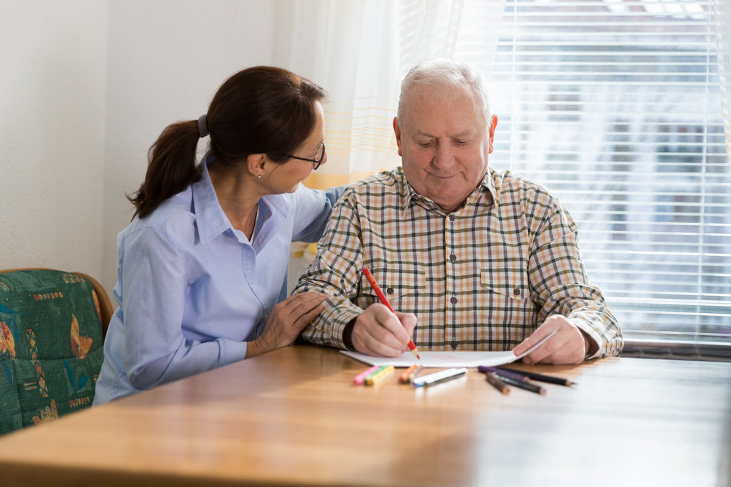 woman working with elderly man on cognitive functions