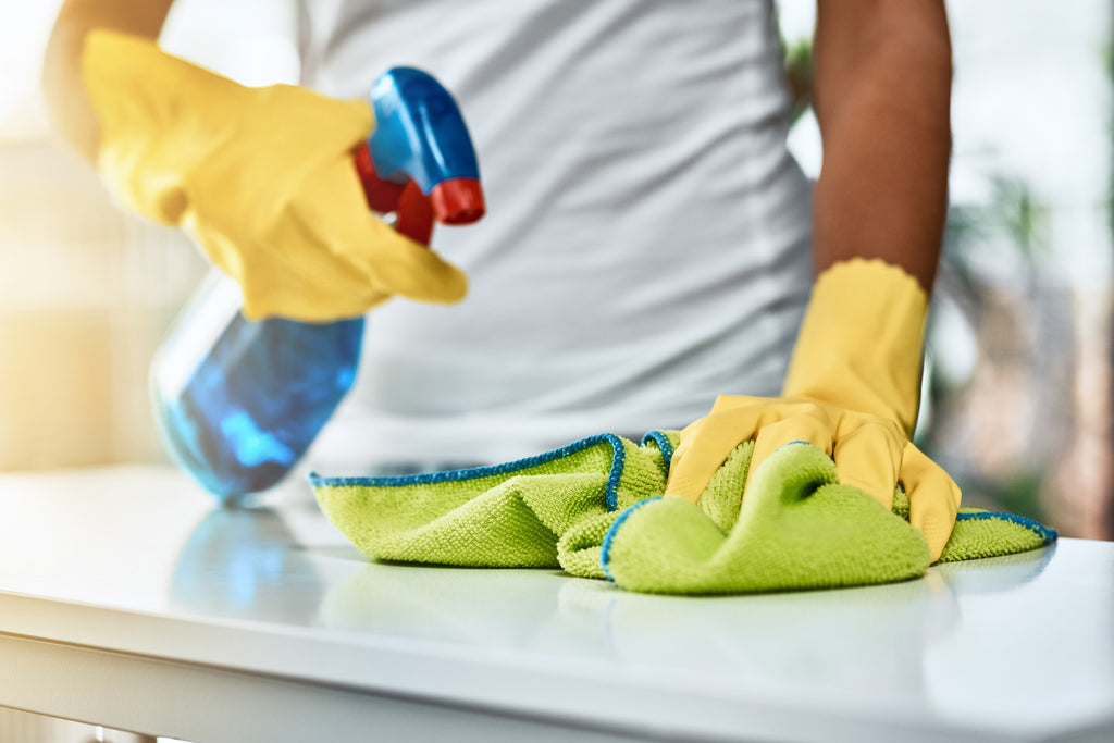 woman cleaning counters with cleaning product in spray bottle