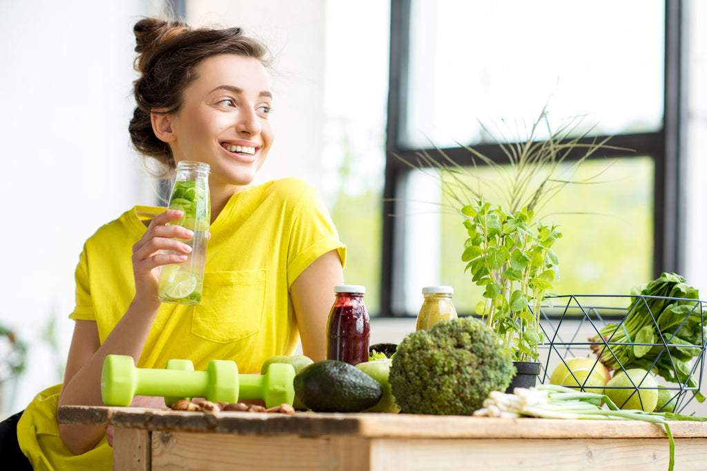 Woman drinking detox drink of fresh greens - Ultimate Body Cleanse