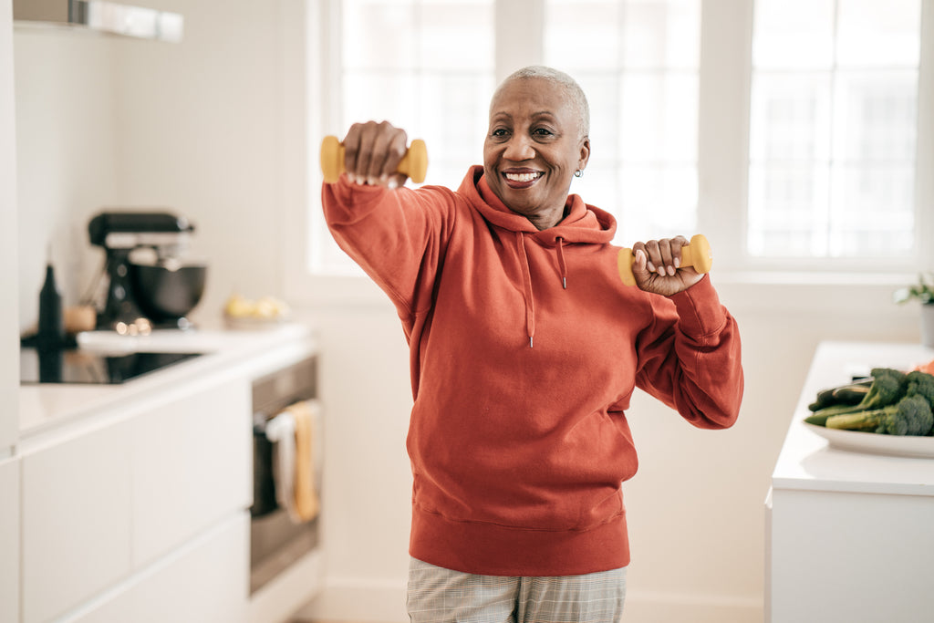 black woman in kitchen exercising with weights to build a strong immune system