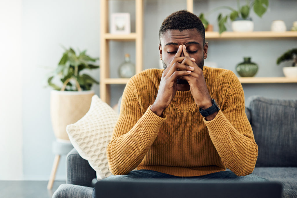 black man sitting on couch holding his sinuses fighting a cold or virus