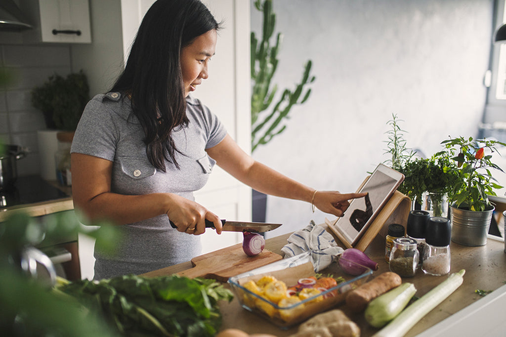Asian woman cooking a healthy meal with fresh greens in a kitchen