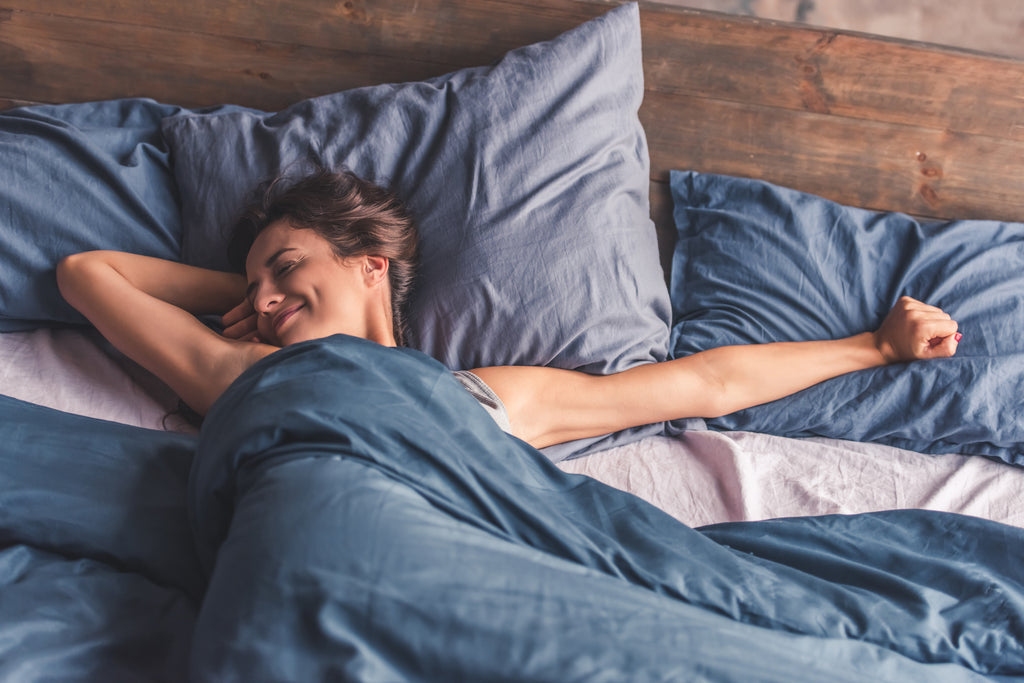 woman stretching awake in bed after a good night sleep