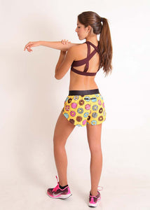 "ChicknLegs women's donuts 1.5"" split running shorts back view with zipper pocket while doing arm stretch."