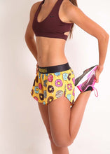 "ChicknLegs women's donuts 1.5"" split running shorts side view while doing hamstring stretch."