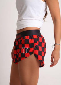 "ChicknLegs women's checkerboard 1.5"" split running shorts side view showcasing our logo and side split."