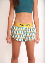 "ChicknLegs women's trippy pineapple 1.5"" split running shorts front view with green sports bra."