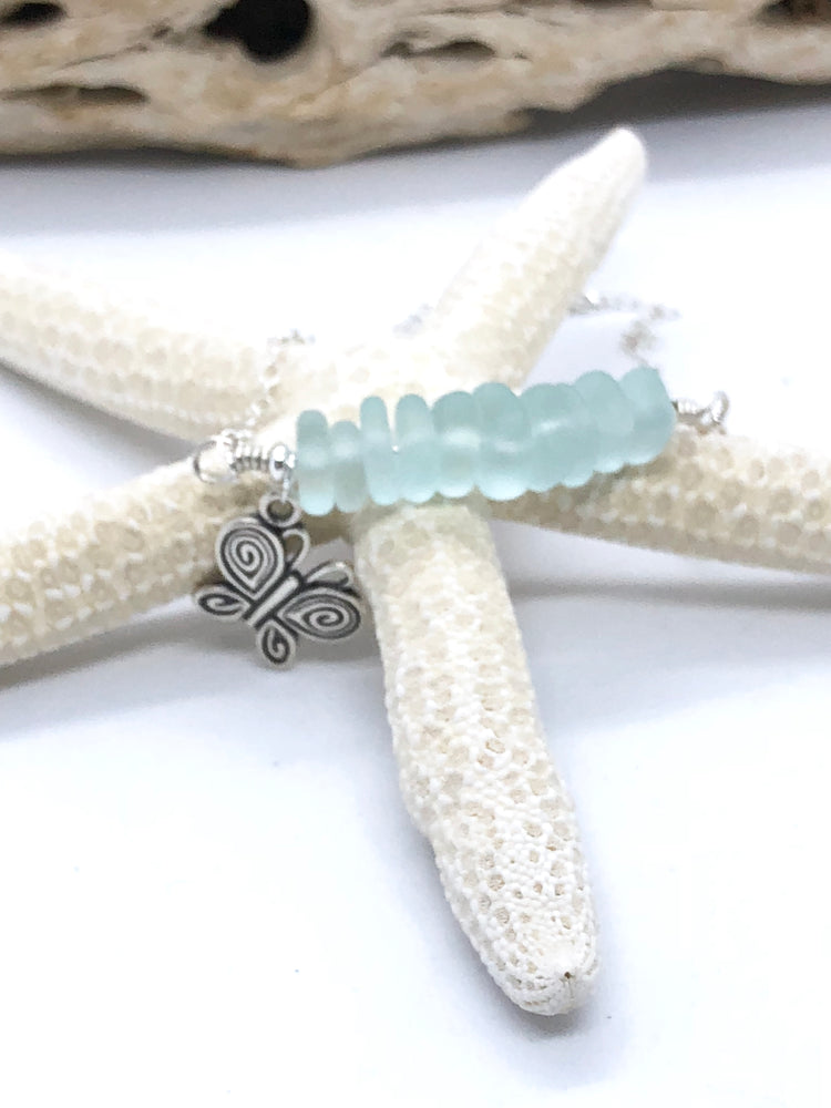 A silver butterfly charm and recycled sea glass wire wrapped onto a sterling silver anklet
