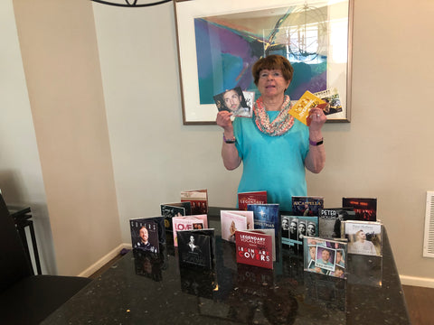 Janie wears a bright teal top and stands behind a table full of Legendary Vocals albums beautifully displayed.