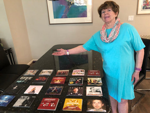 Janie stands to the right of her dining room table in a bright teal dress. Her arm is extended over the table, upon which lies a large collection of Legendary Vocals albums.