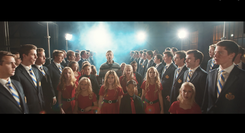 Groups of boys in blue suits line the sides of the space, as young girls in red dresses walk between them with Peter Hollens behind them. Everyone is singing and there are bright lights in the back that create lens flares.