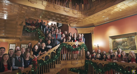 Peter Hollens and the kids of OVCC stand on stairways and landings in a grand, wood-paneled room decorated for Christmas.