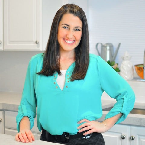 Image of Rachel Farnsworth in a turquoise blouse, smiling and standing in a bright kitchen.