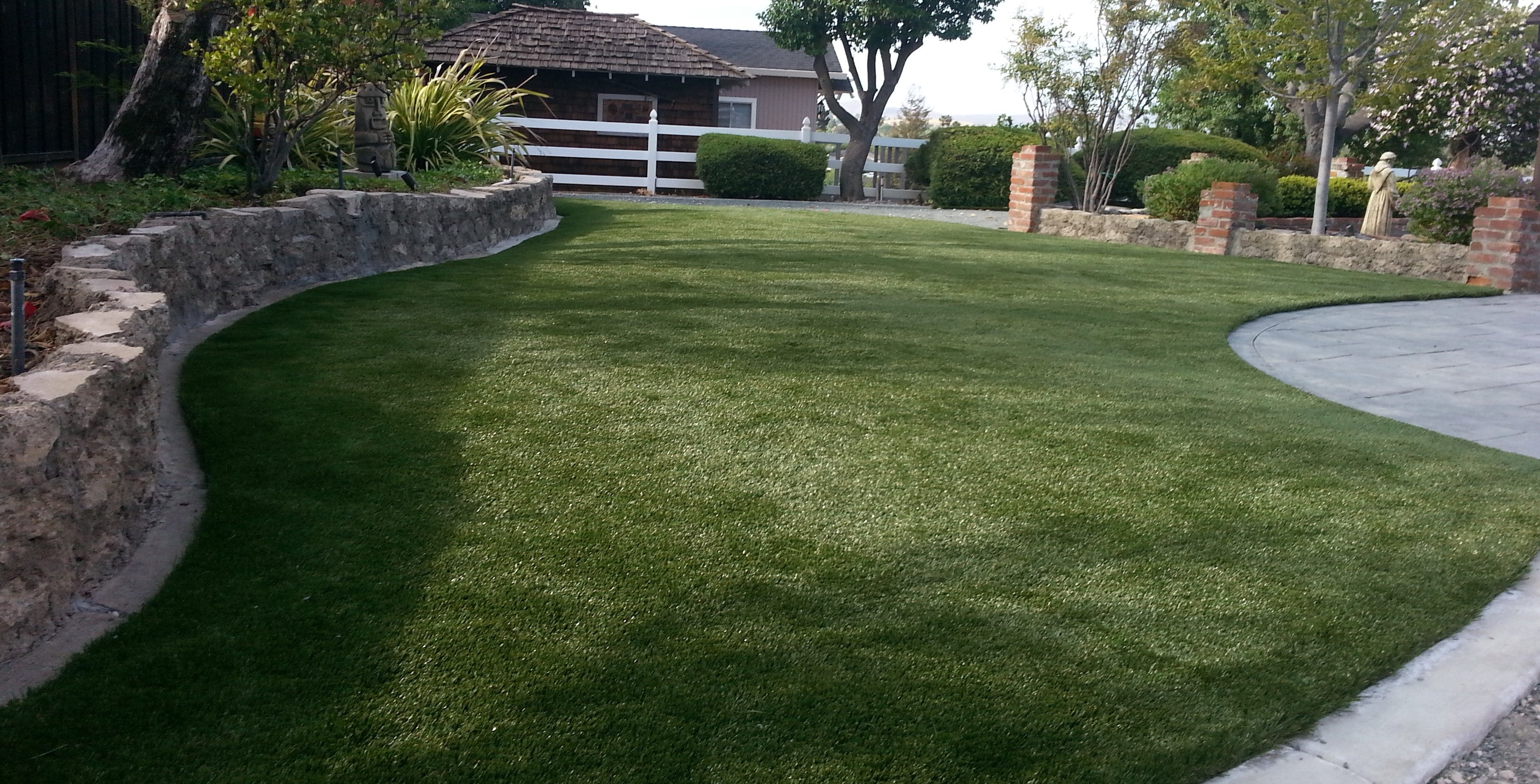 Turf installed between a stone wall and a driveway in a client's front yard.