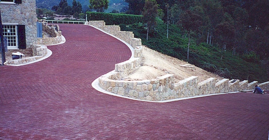 Red interlocking rubber pavers installed on a winding driveway.