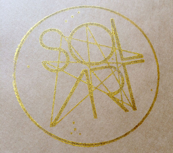 A gold stamp of Solart's first logo design, stamped onto brown recycled kraft paper.