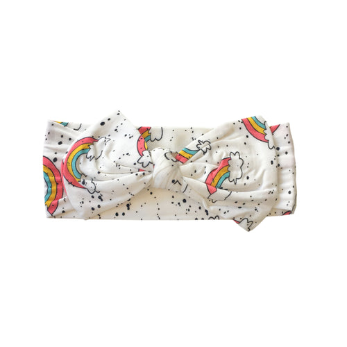 A soft, knotted headband for infants with pink, yellow and turquoise rainbows and a hint of splatter paint design.