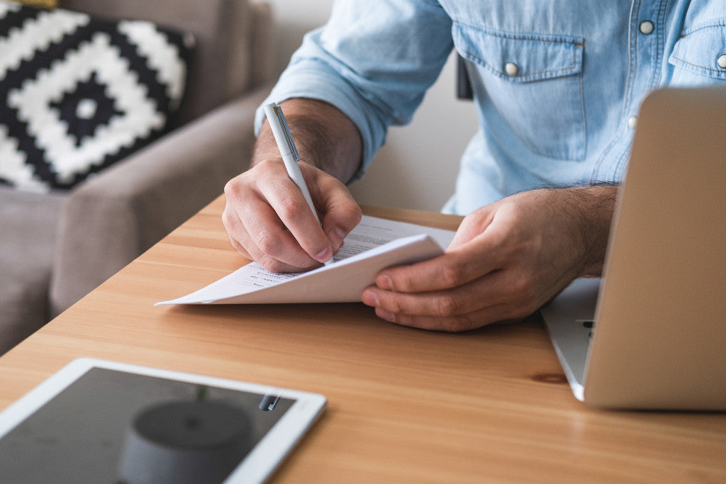 Man writing down positive affirmations