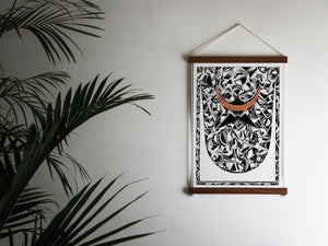 geometric print hanging next to palm leaves