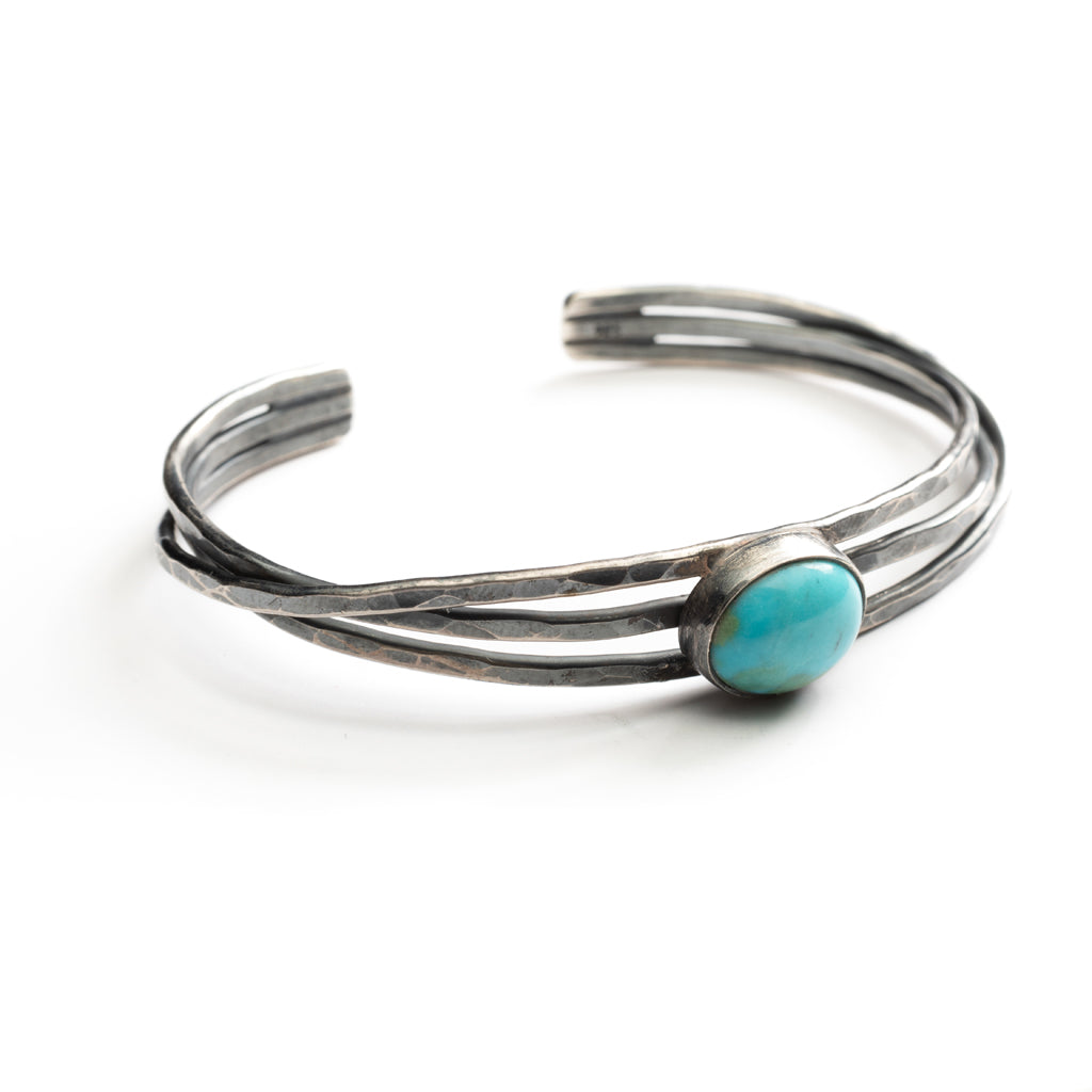 3 hand hammered silver bands hold a turquoise stone