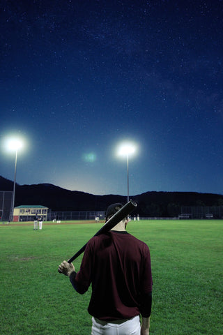 man facing baseball field with bat alone at night under the lights